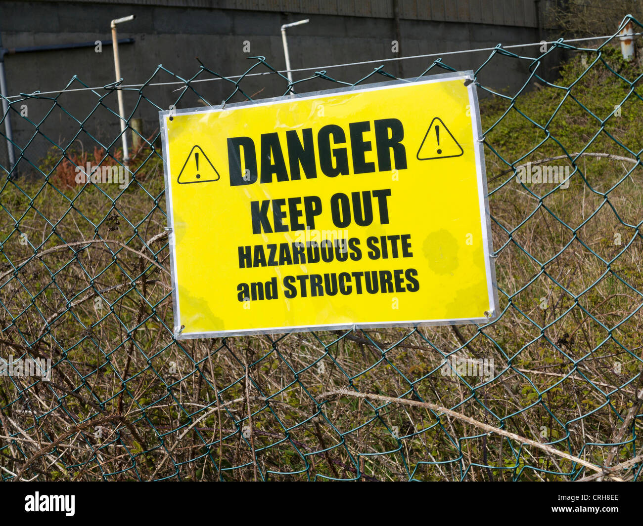 Danger Keep Out sign outside a derelict factory complex - Stock Image