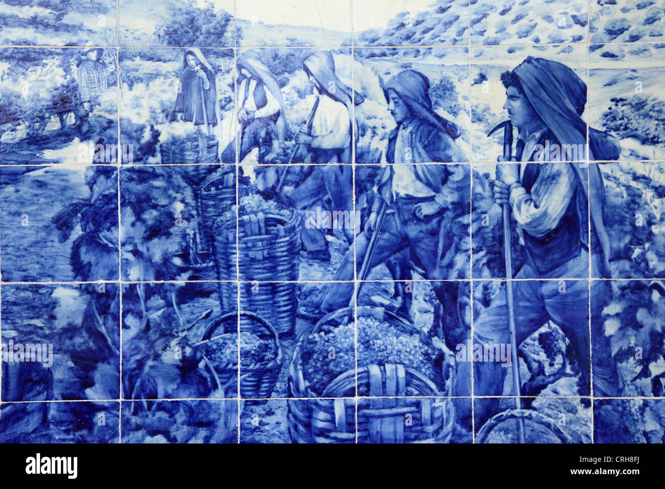 The grape harvest is depicted on azulejo tiles at the railway station in Pinhao, Portugal. - Stock Image