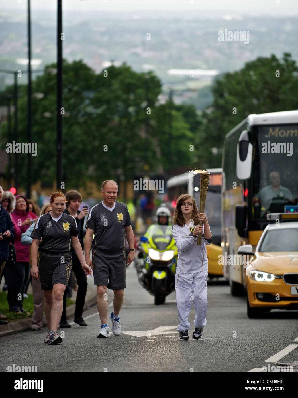 12 yr old. Catherine Stott carries the flame through the town of Oldham, as part of the Olympic torch relay - Stock Image