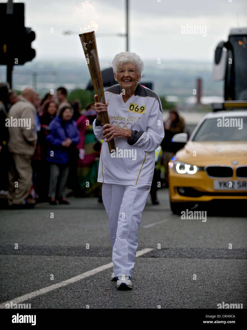 94yr old Thora Beddard, carries the Olympic flame through the town of Oldham as part of the torch relay. - Stock Image