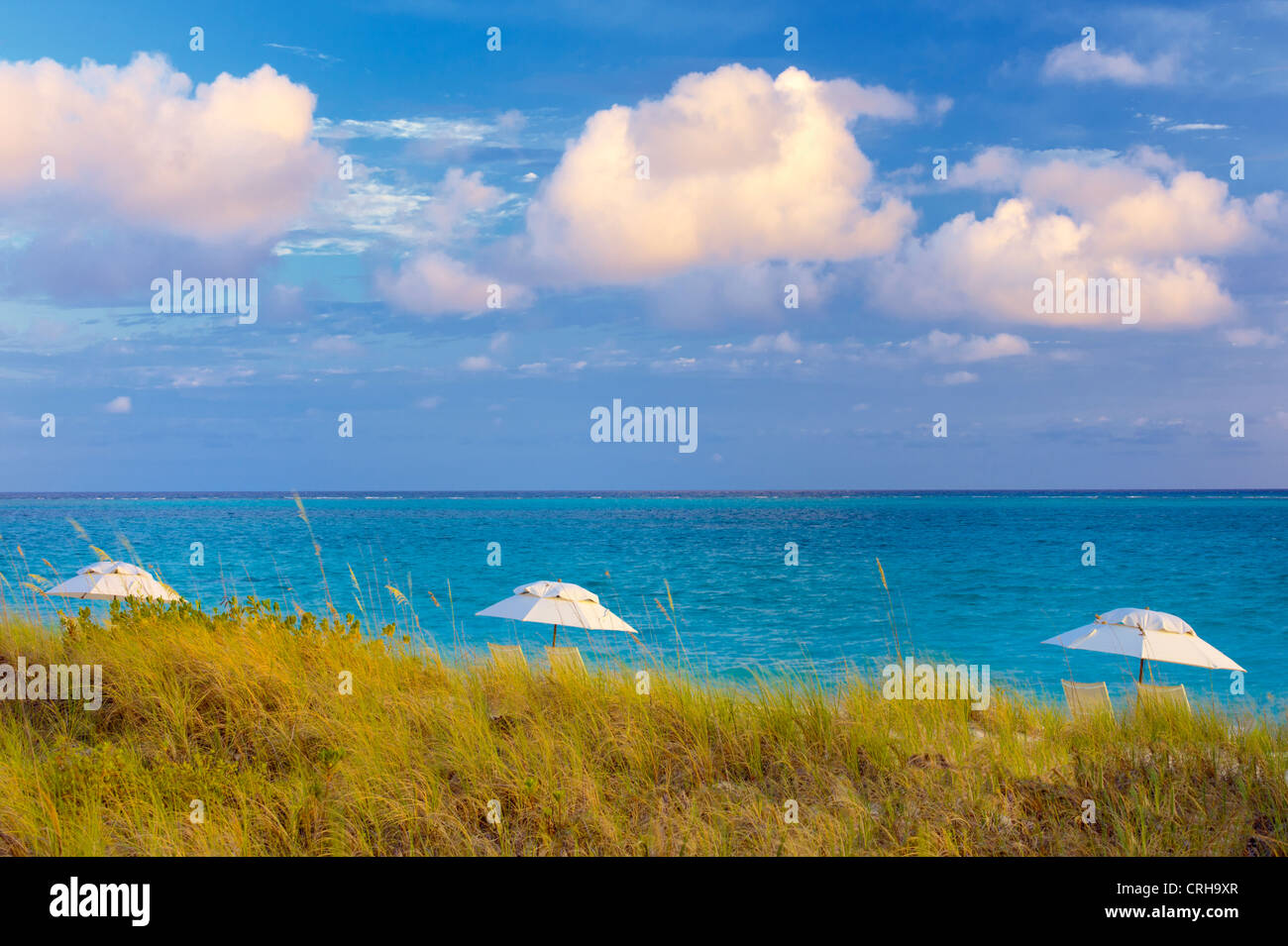 Three umbrellas and three clouds. Grace Bay, Providenciales. Turks and Caicos. Stock Photo