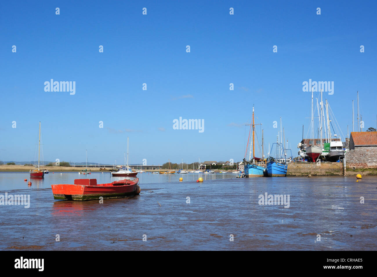 Red and blue hulled boats, moored in the estuary and at the quayside at low tide, Topsham, Devon, England, UK - Stock Image