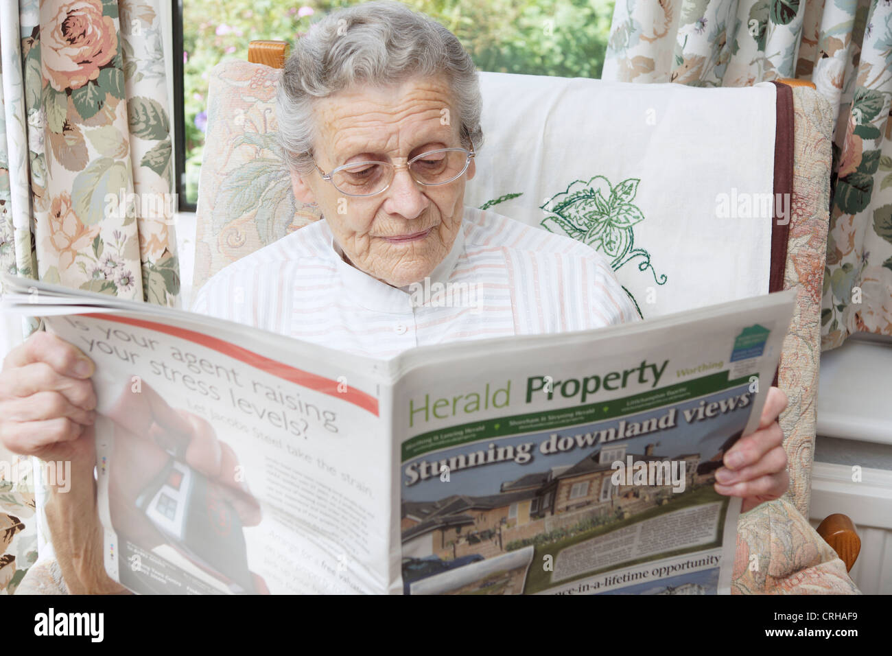 Elderly woman looking at properties on the property pages in a local paper Stock Photo