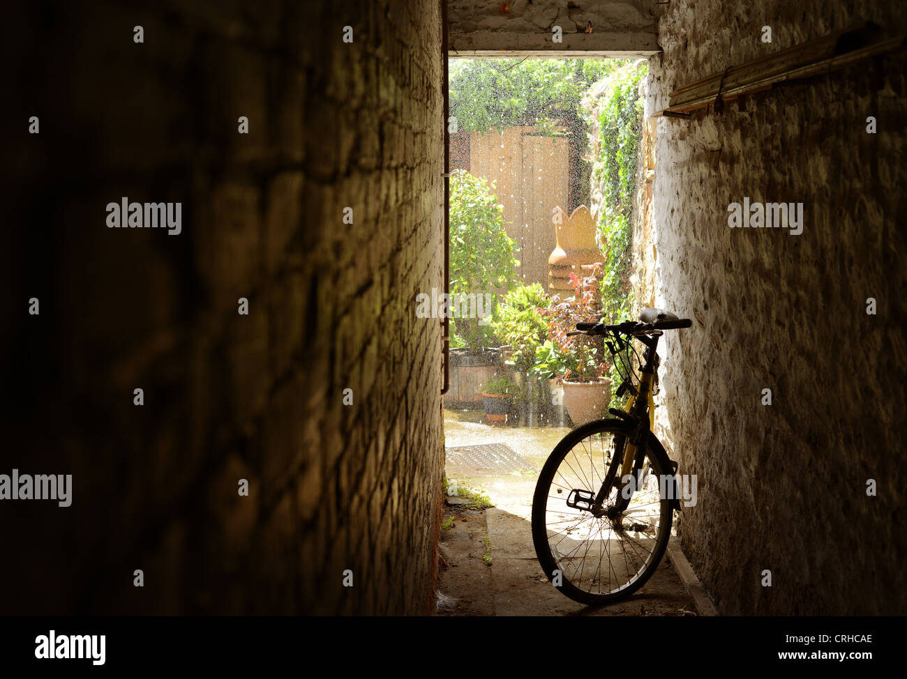 Bicycle sheltered from heavy rain in alleyway at side of house. Taken during a sudden downpour on a sunny day. - Stock Image