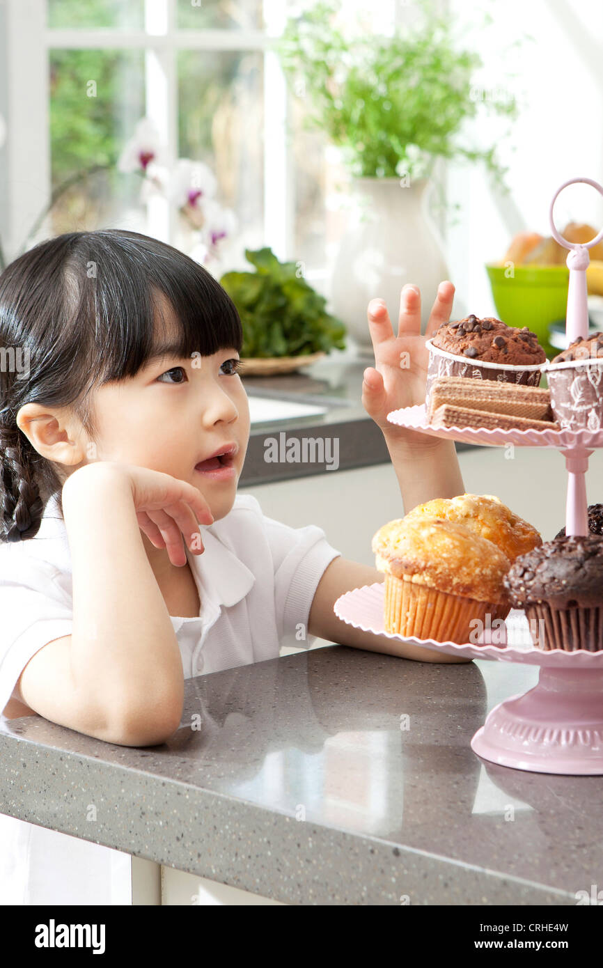 Little girl waiting for muffin - Stock Image