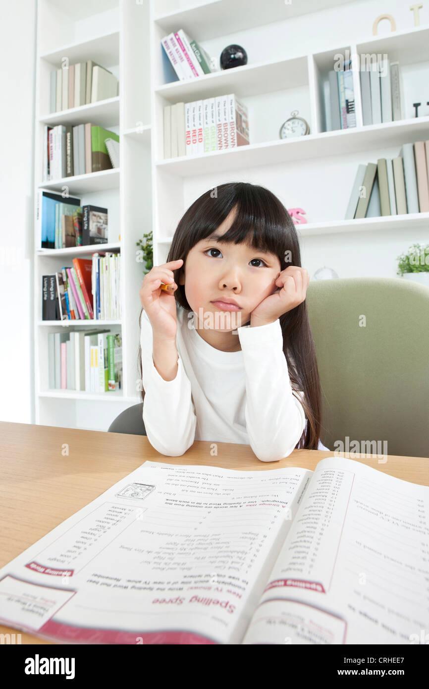 Little girl studying at desk - Stock Image