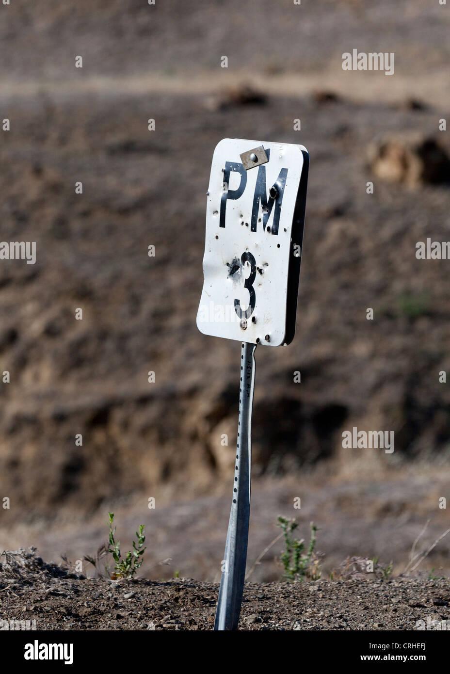 Bullet ridden road sign Stock Photo