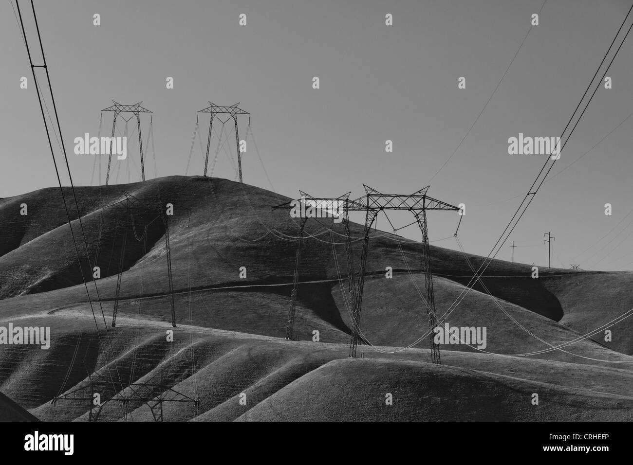 Pylons and power lines over barren hills - California, USA - Stock Image