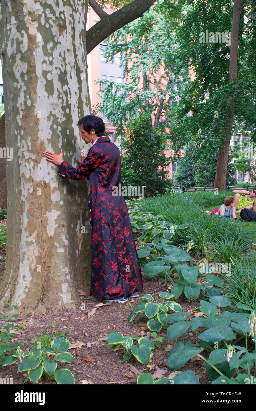 A tree hugger in an exotic colorful robe hugs a tree in Washington Square Park, Greenwich Village, New York - Stock Image