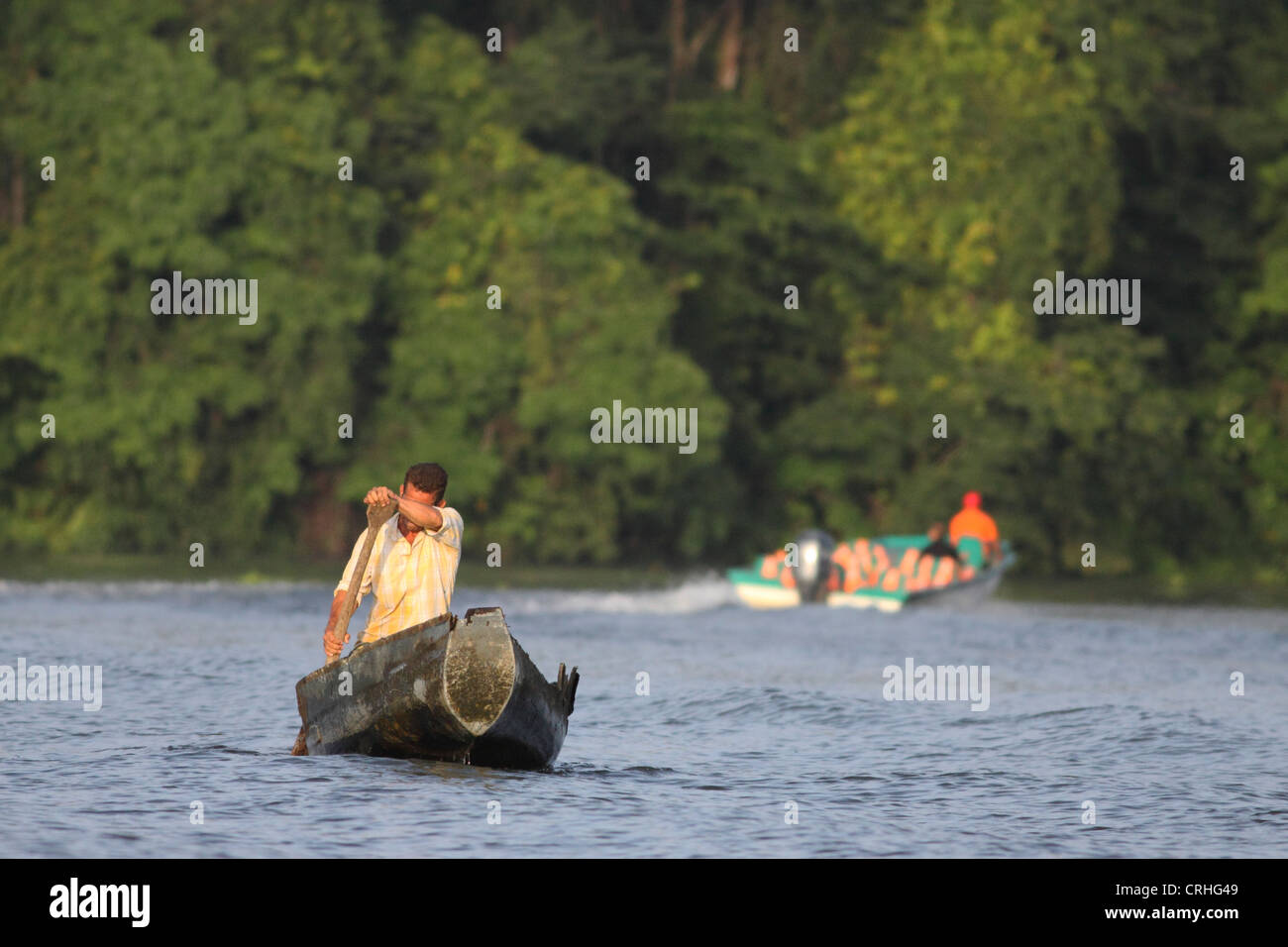 Tourist boat passes villager in canoe on natural rainforest canal. Tortuguero National Park. Costa Rica. October - Stock Image