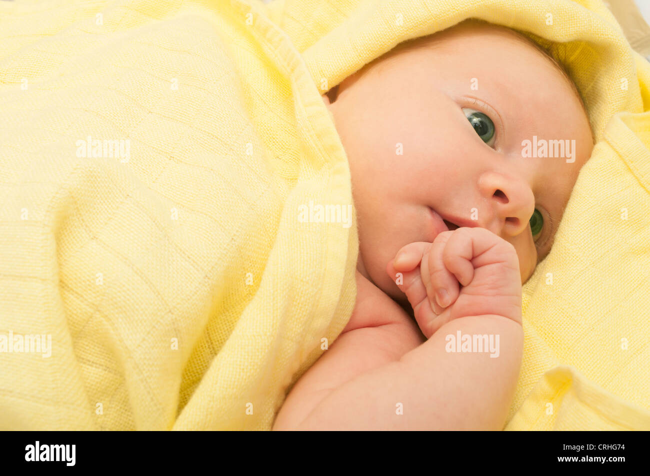 Newborn Baby in the Bed under Yellow Blanket - Stock Image