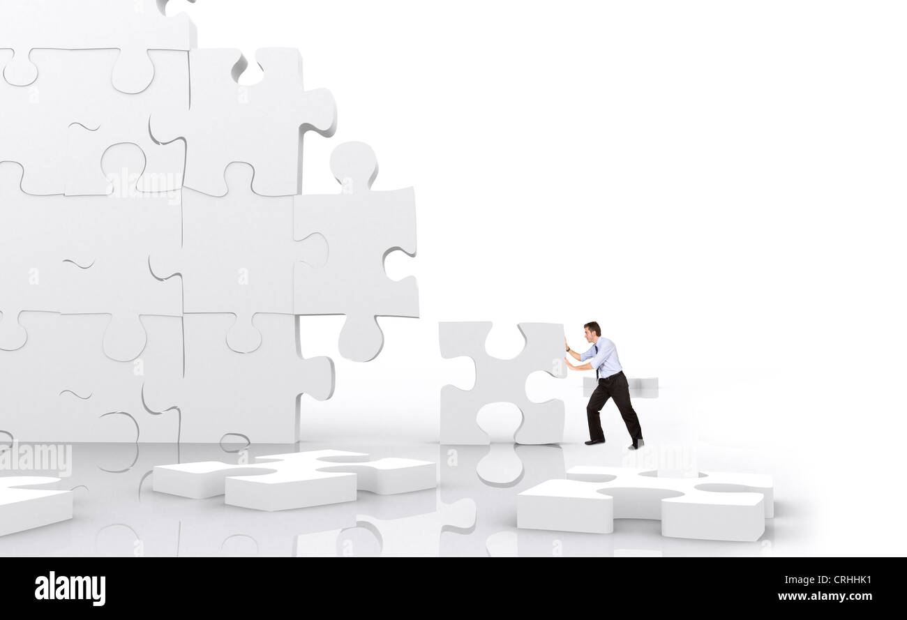 young man fitting a giant puzzle piece into huge puzzle wall klein