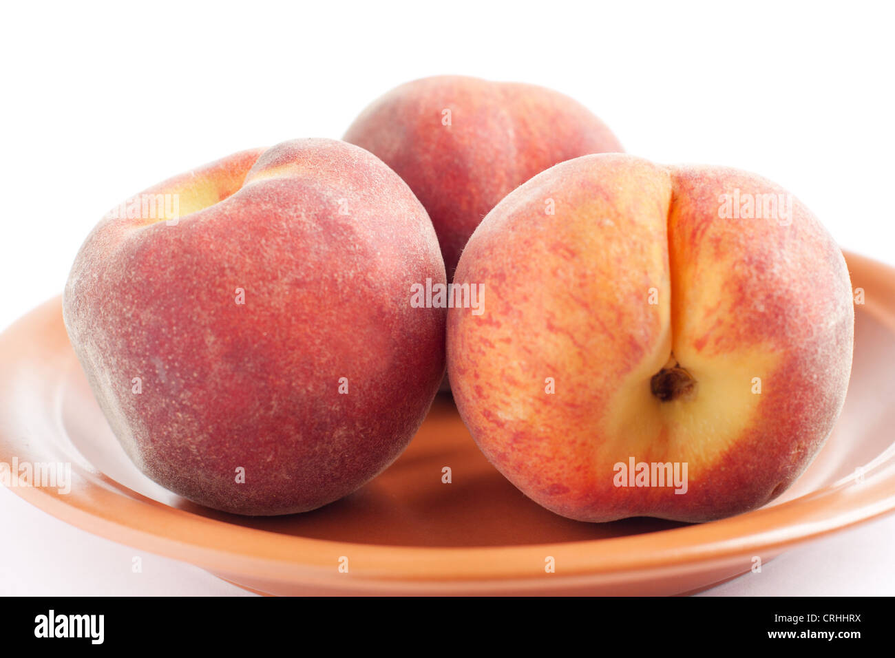Three ripe peach on a ceramic plate - Stock Image