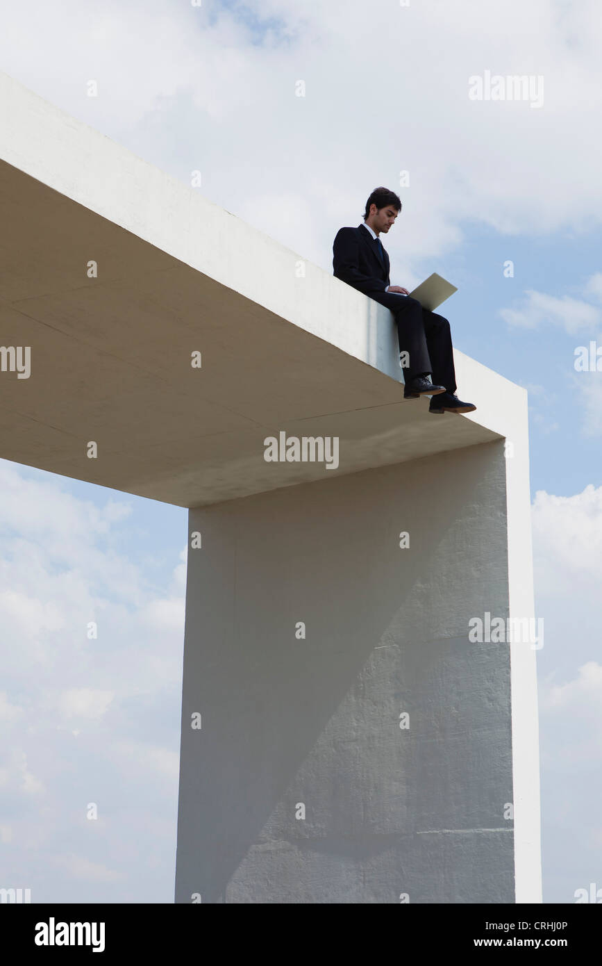 Businessman sitting on top of tall structure using laptop computer - Stock Image