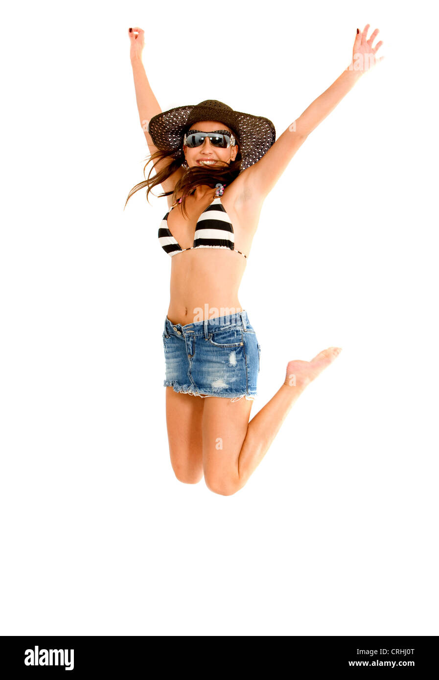young woman in bikini, jeans miniskirt, sunglasses and sunhat, cutting a caper - Stock Image