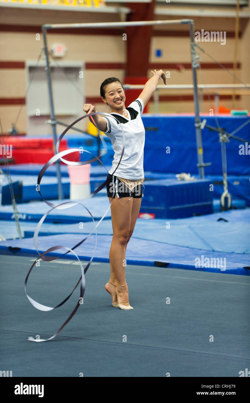 Teenage girl gymnast practicing rhythmic gymnastics, twirling ribbon - Stock Image