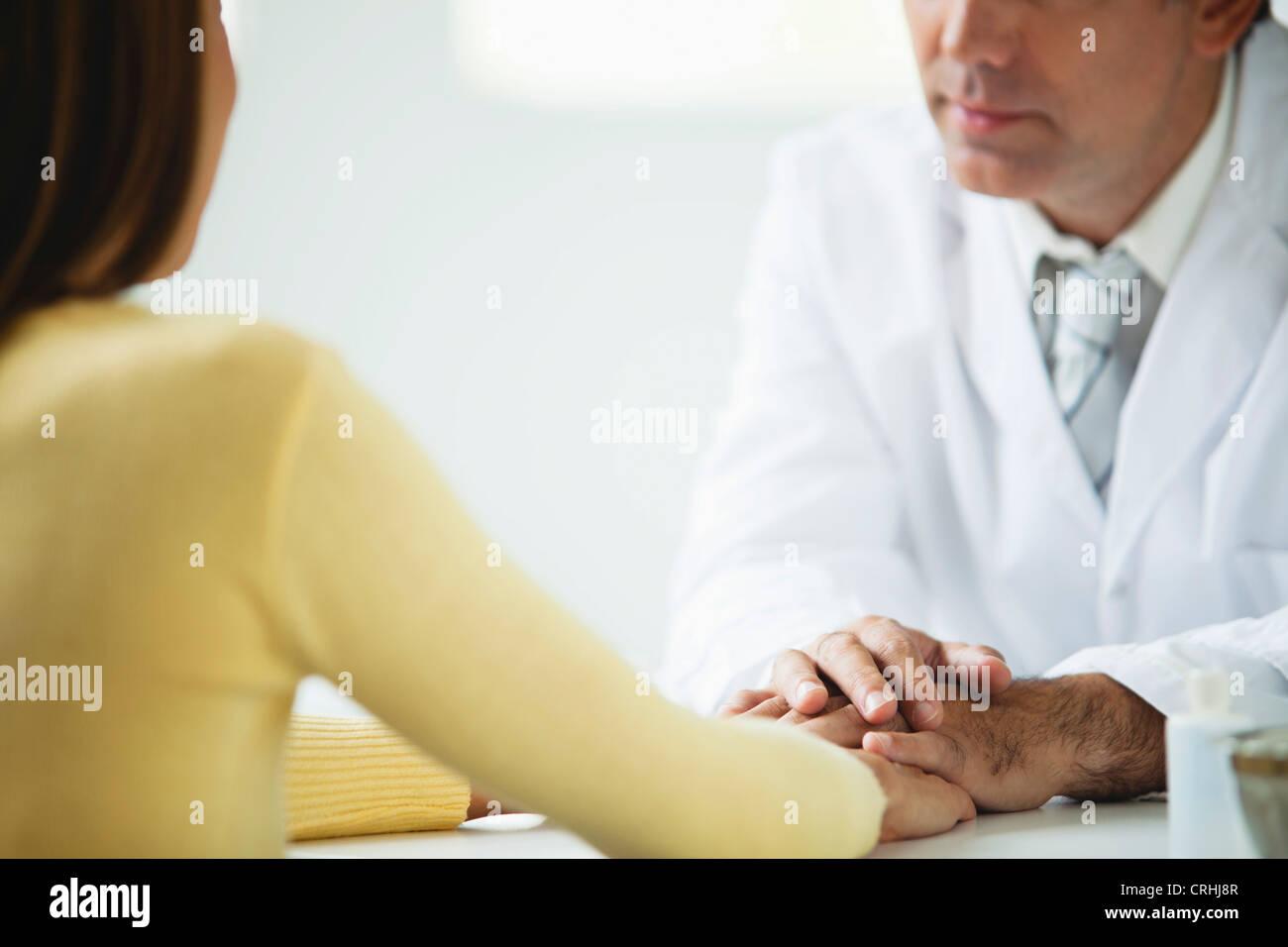 Doctor comforting patient Stock Photo