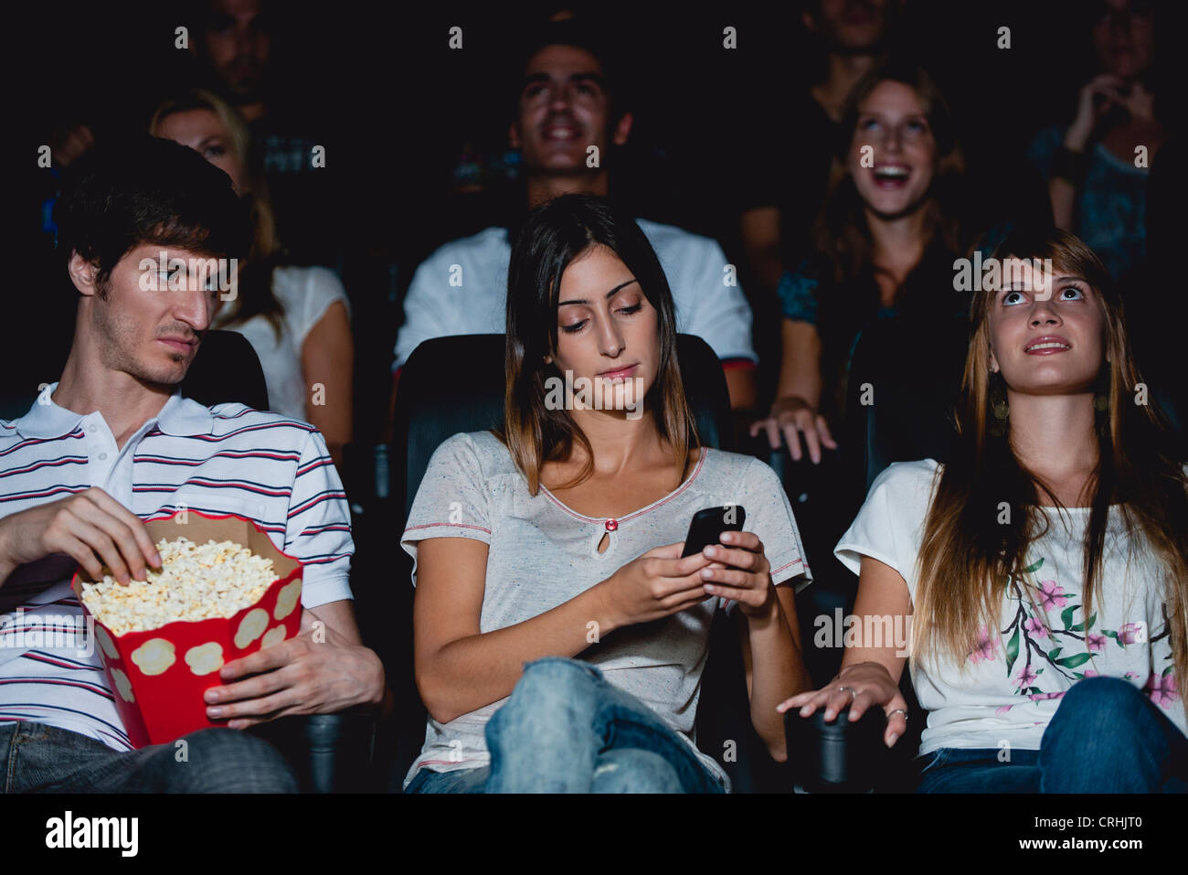 Woman using cell phone in movie theater, man looking over with annoyed expression - Stock Image