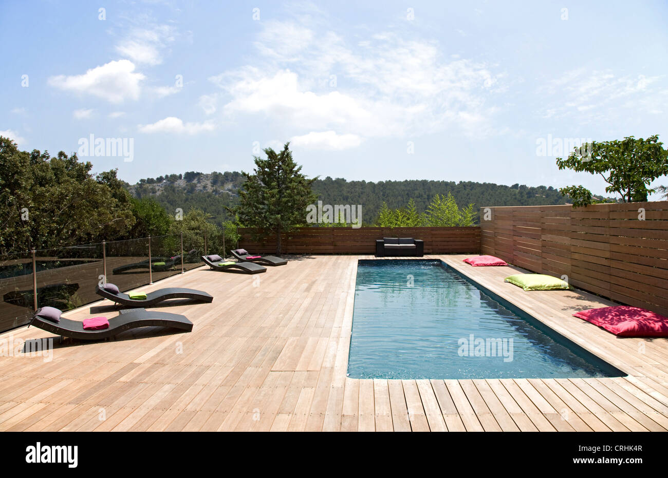 Lawn chairs and pool on modern deck - Stock Image