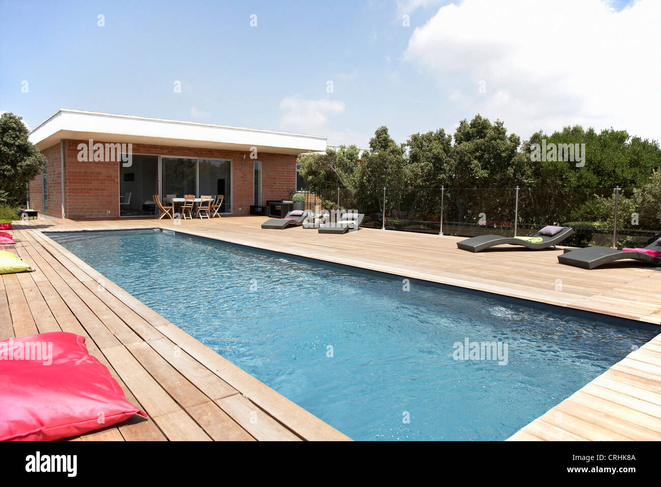 Lawn chairs and pool on modern deck Stock Photo