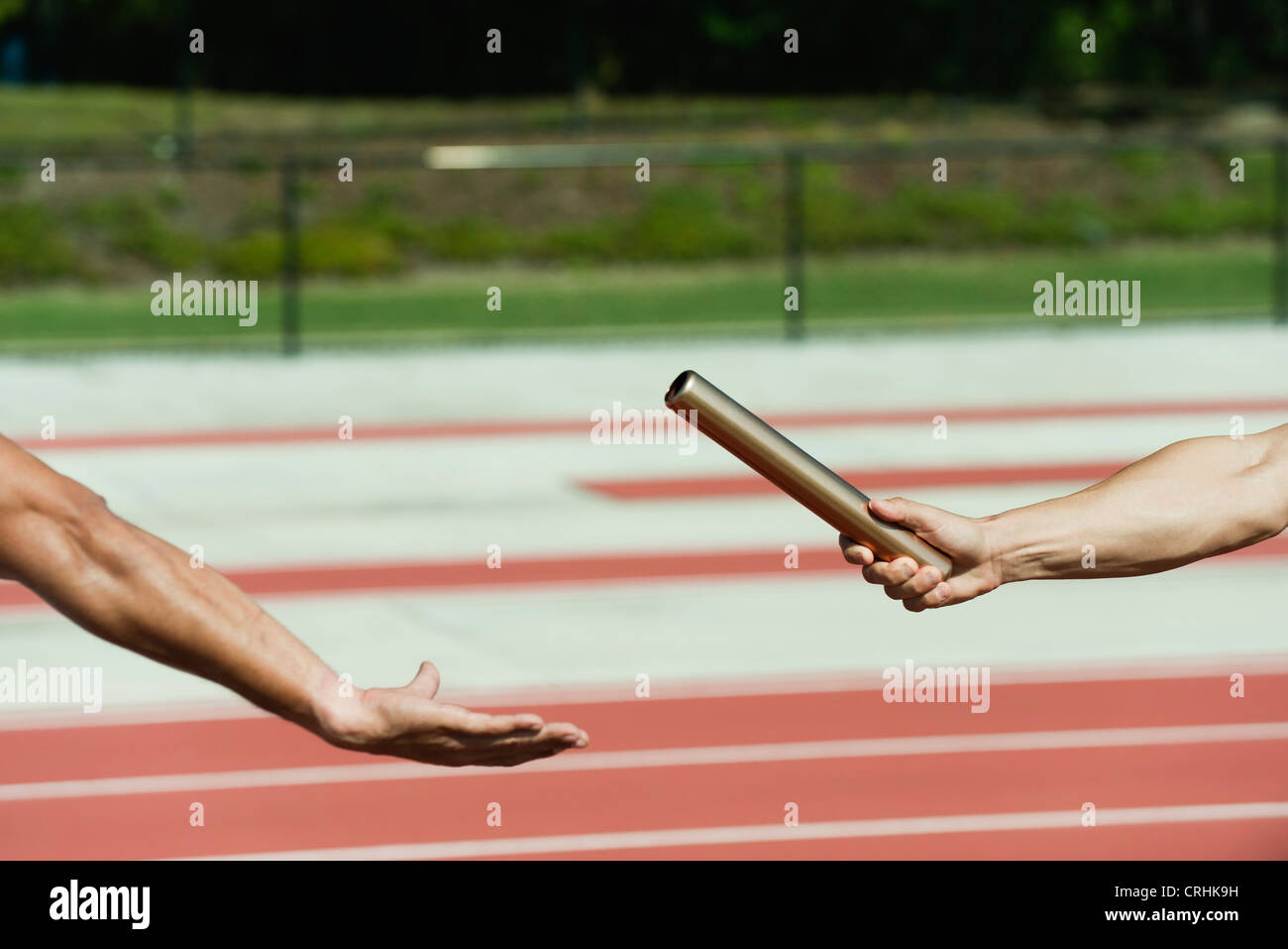 Businessman crouched at starting line on running track - Stock Image
