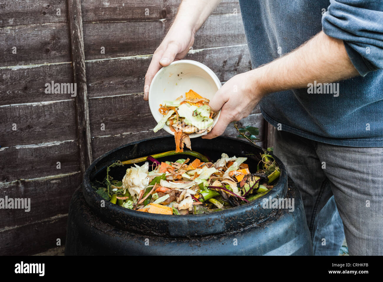 Man adding to compost bin outdoors - Stock Image