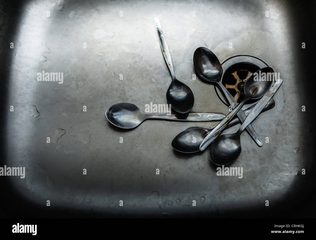Pile of dirty spoons in sink - Stock Image