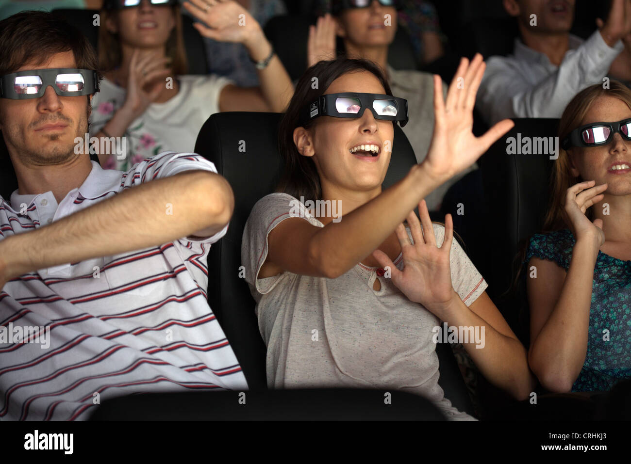 Audience enjoying 3-D movie in theater - Stock Image