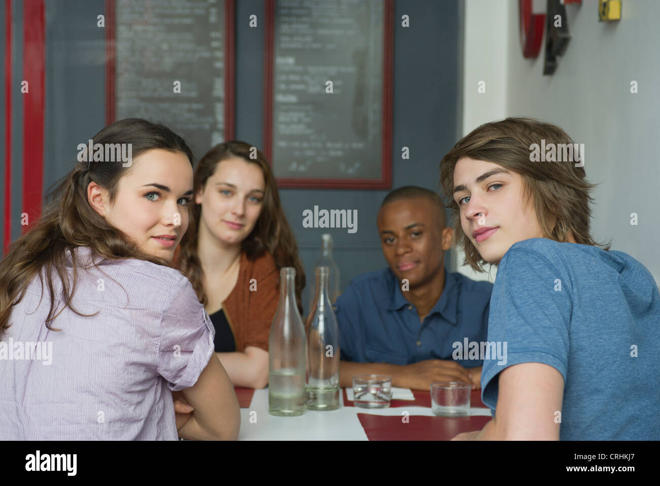 Young adult friends hanging out in cafe - Stock Image