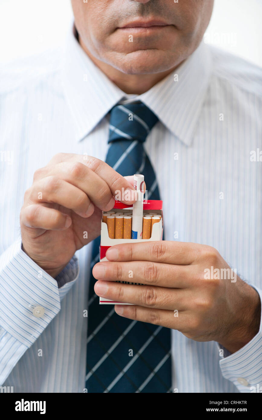 Man removing rolled euro from cigarette pack - Stock Image