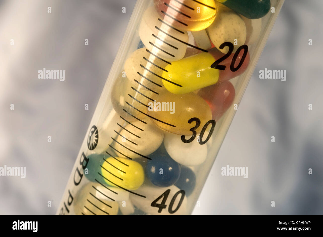 Close up of numerous tablets and pills in a syringe - Stock Image