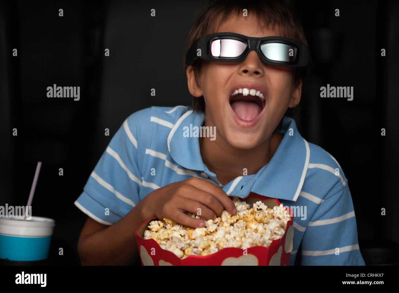 Boy laughing and eating popcorn during 3-D movie in theater - Stock Image