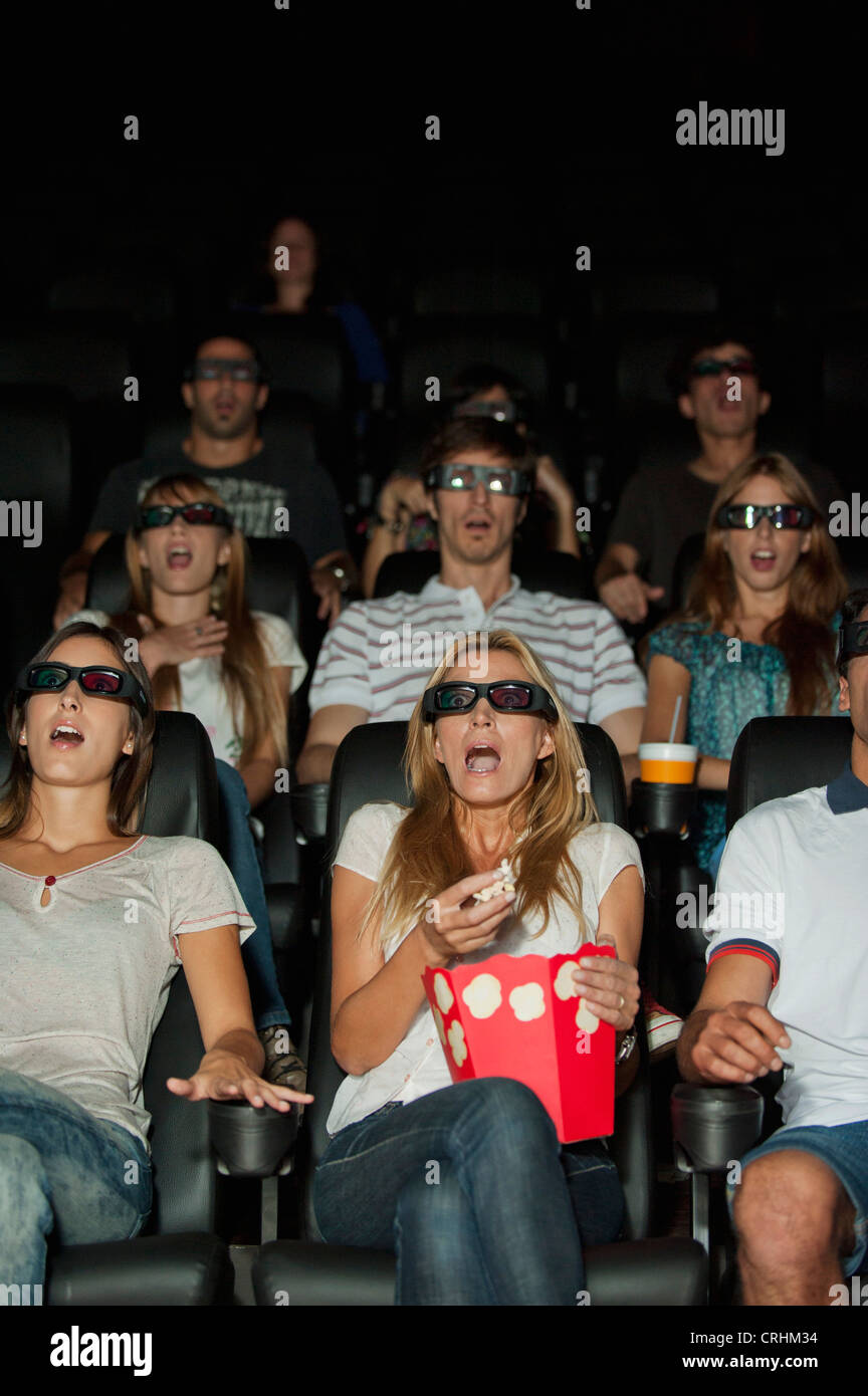 Audience wearing 3-D glasses in movie theater with shocked expressions on faces - Stock Image