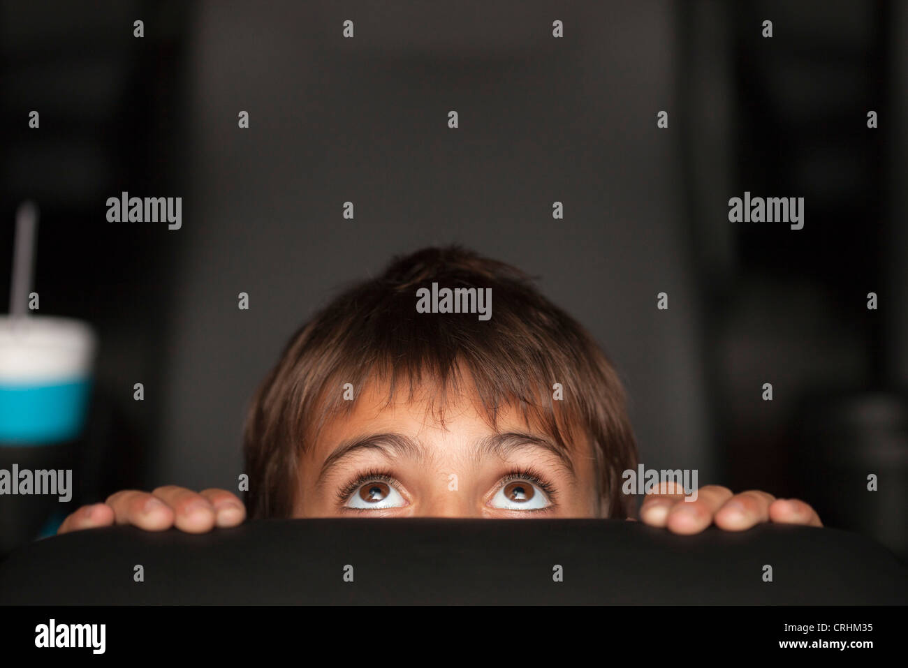 Boy peeking over top of seat during horror movie in theater - Stock Image