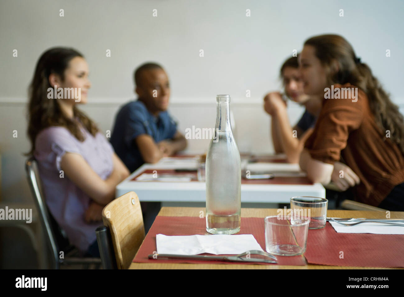 Friends hanging out in cafe, focus on empty table in foreground - Stock Image