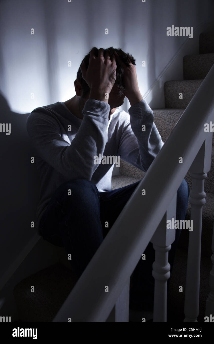 Young man sitting on the stairs, his hands on his head in despair. - Stock Image