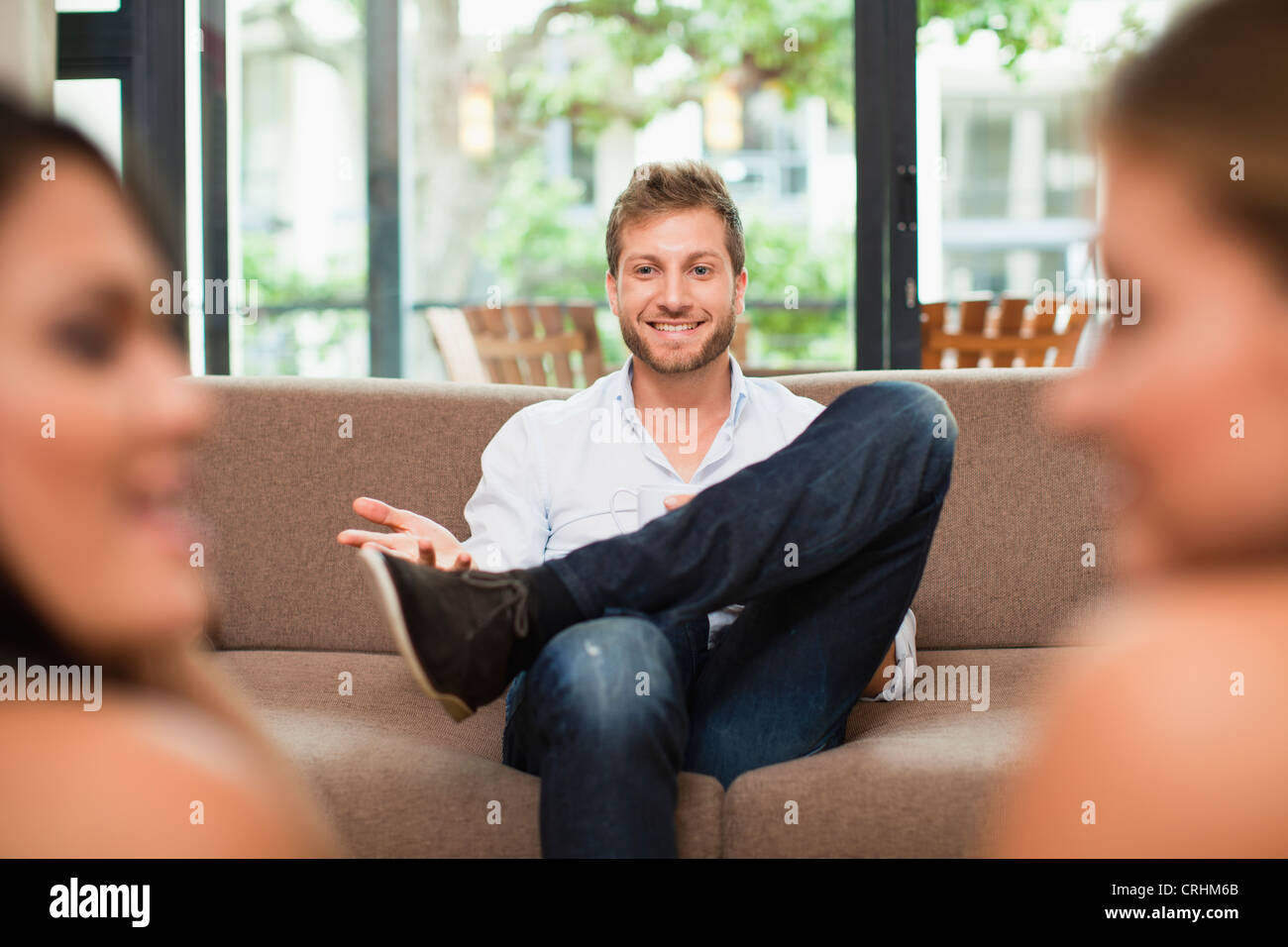 Man talking to women on sofa - Stock Image