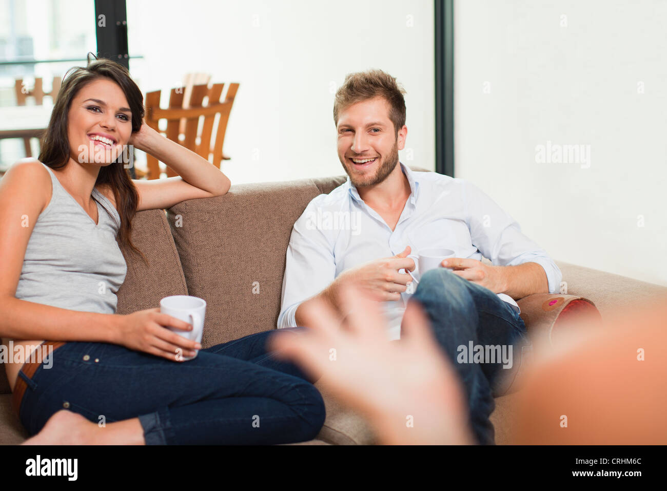 Couple having coffee together on sofa - Stock Image