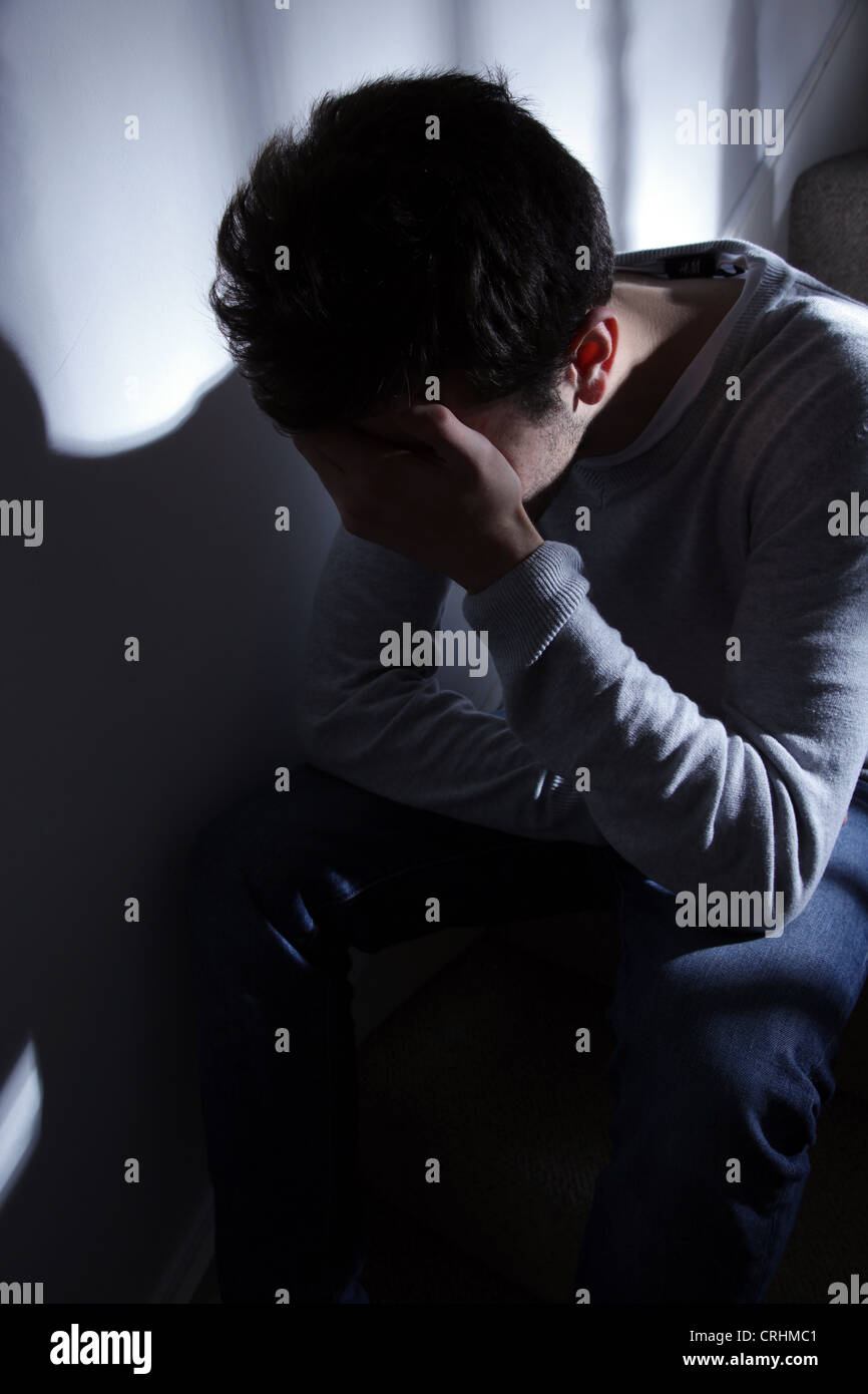 Young man sitting on the stairs, his hand covering his face. - Stock Image