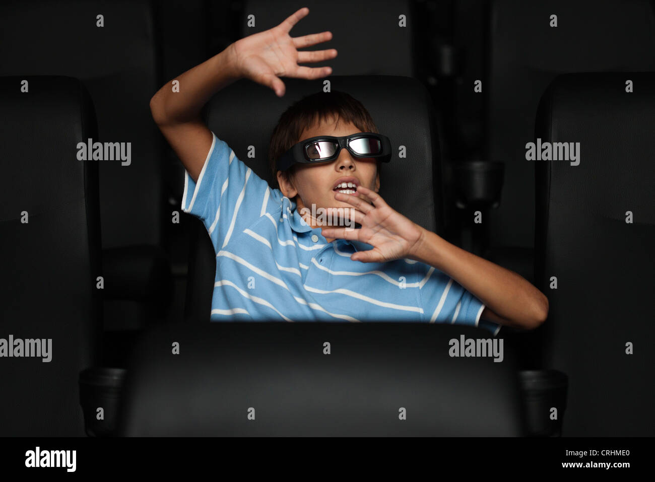 Boy watching 3-D horror movie in theater - Stock Image