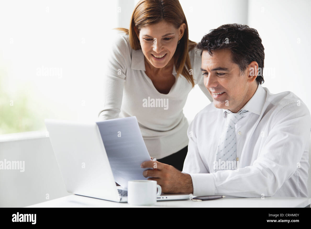 Business colleagues looking at laptop computer together - Stock Image