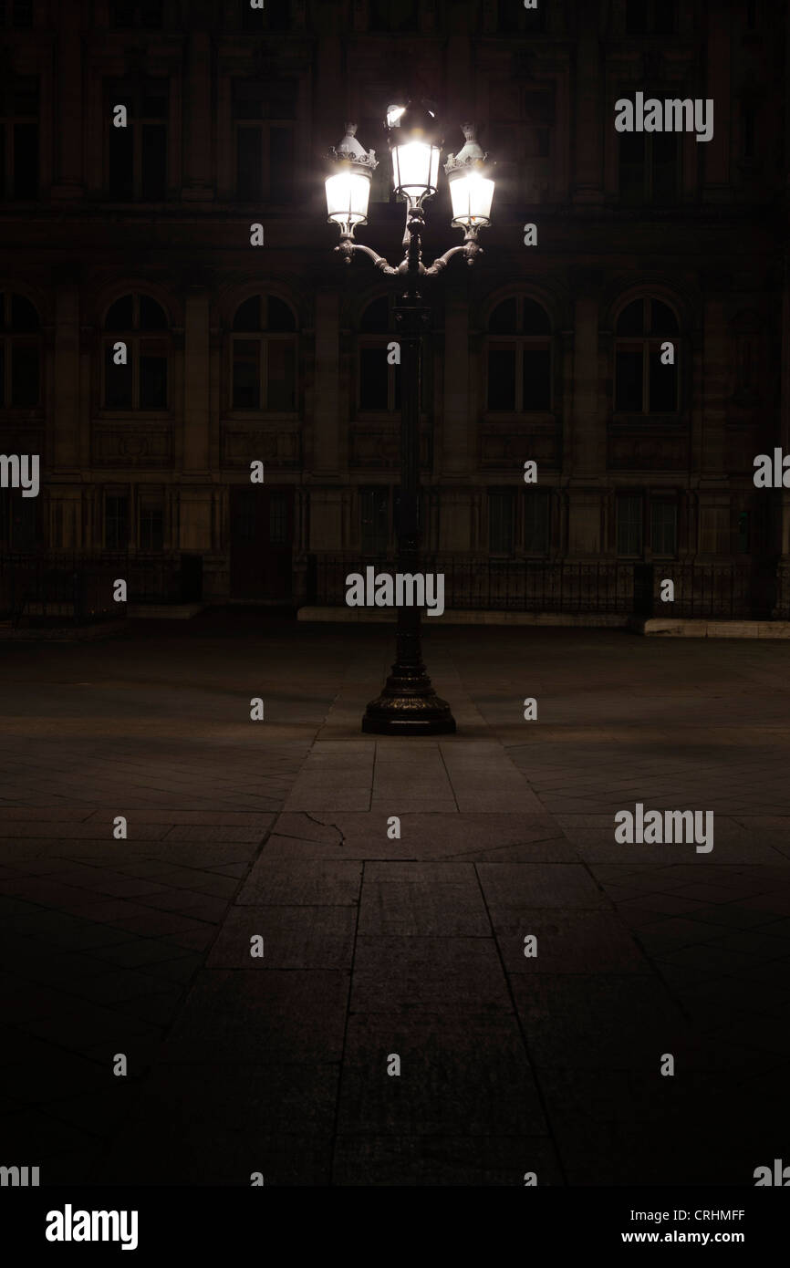 Street lamp illuminated at night in Place de l'Hotel de Ville, Paris, France - Stock Image