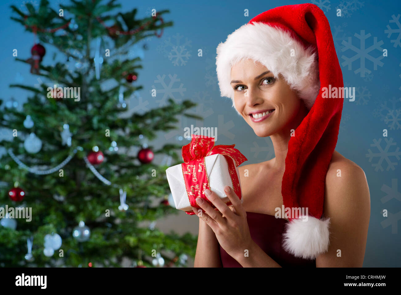 Woman wearing Santa hat and holding Christmas present, portrait - Stock Image