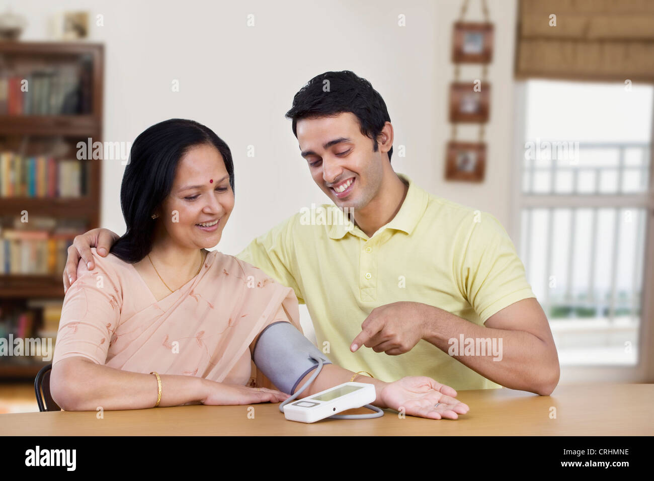 Young man sitting with mother pointing at blood pressure gauge - Stock Image
