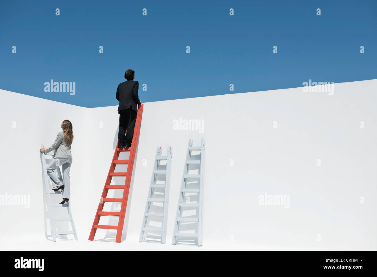 Businessman and businesswoman climbing ladders - Stock Image