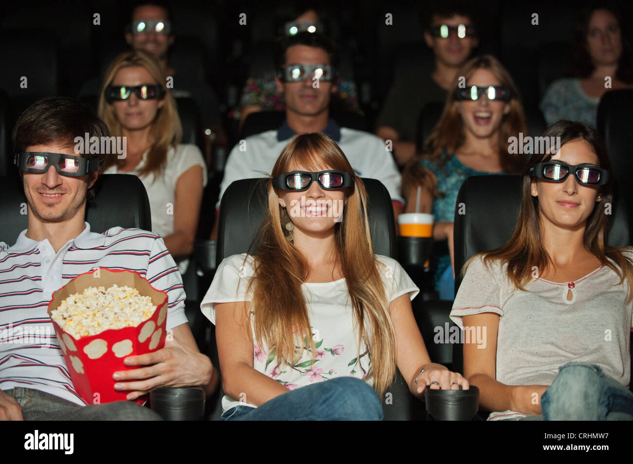 Audience wearing 3-D glasses in movie theater - Stock Image