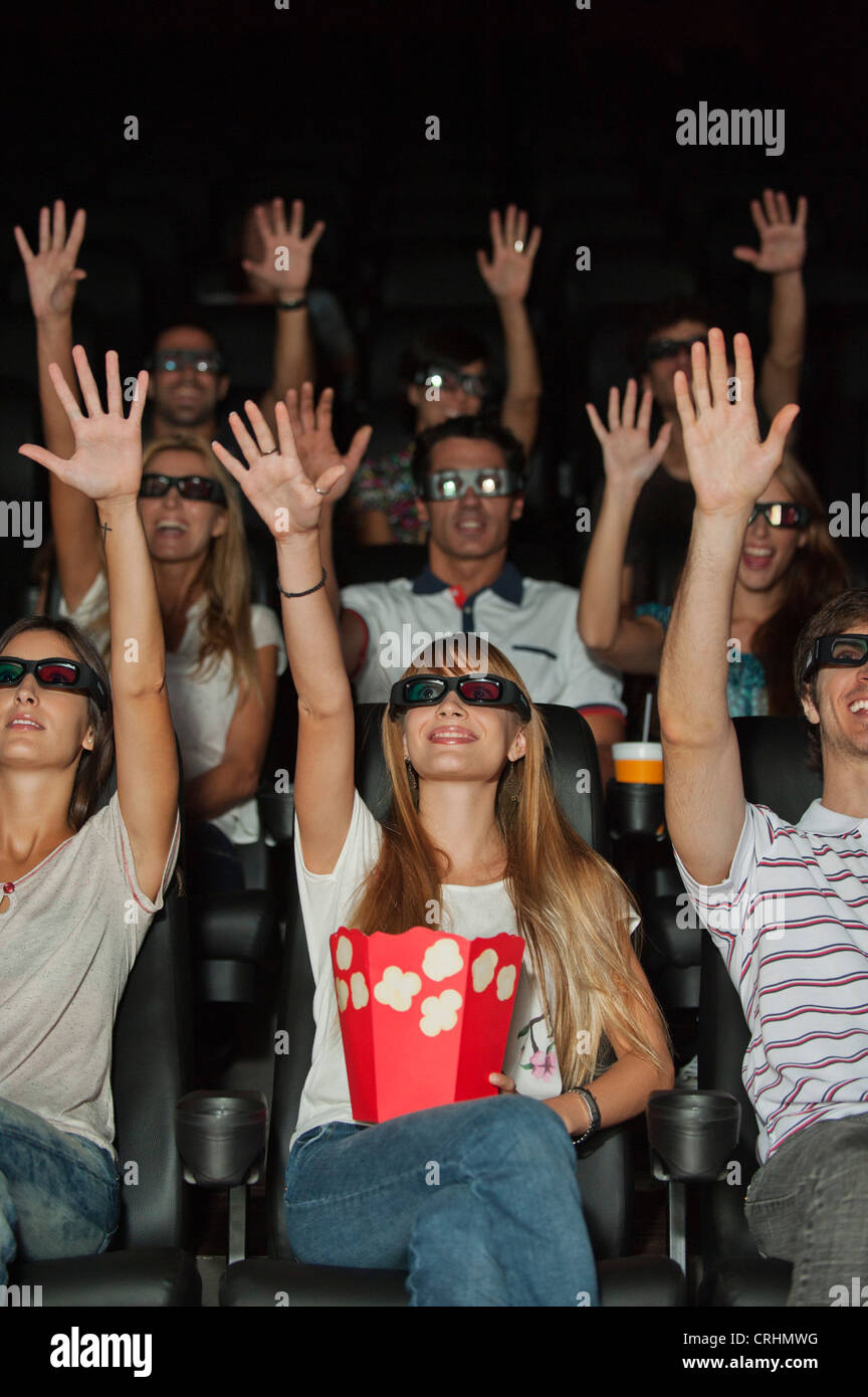 Audience wearing 3-D glasses in movie theater, arms reaching up - Stock Image