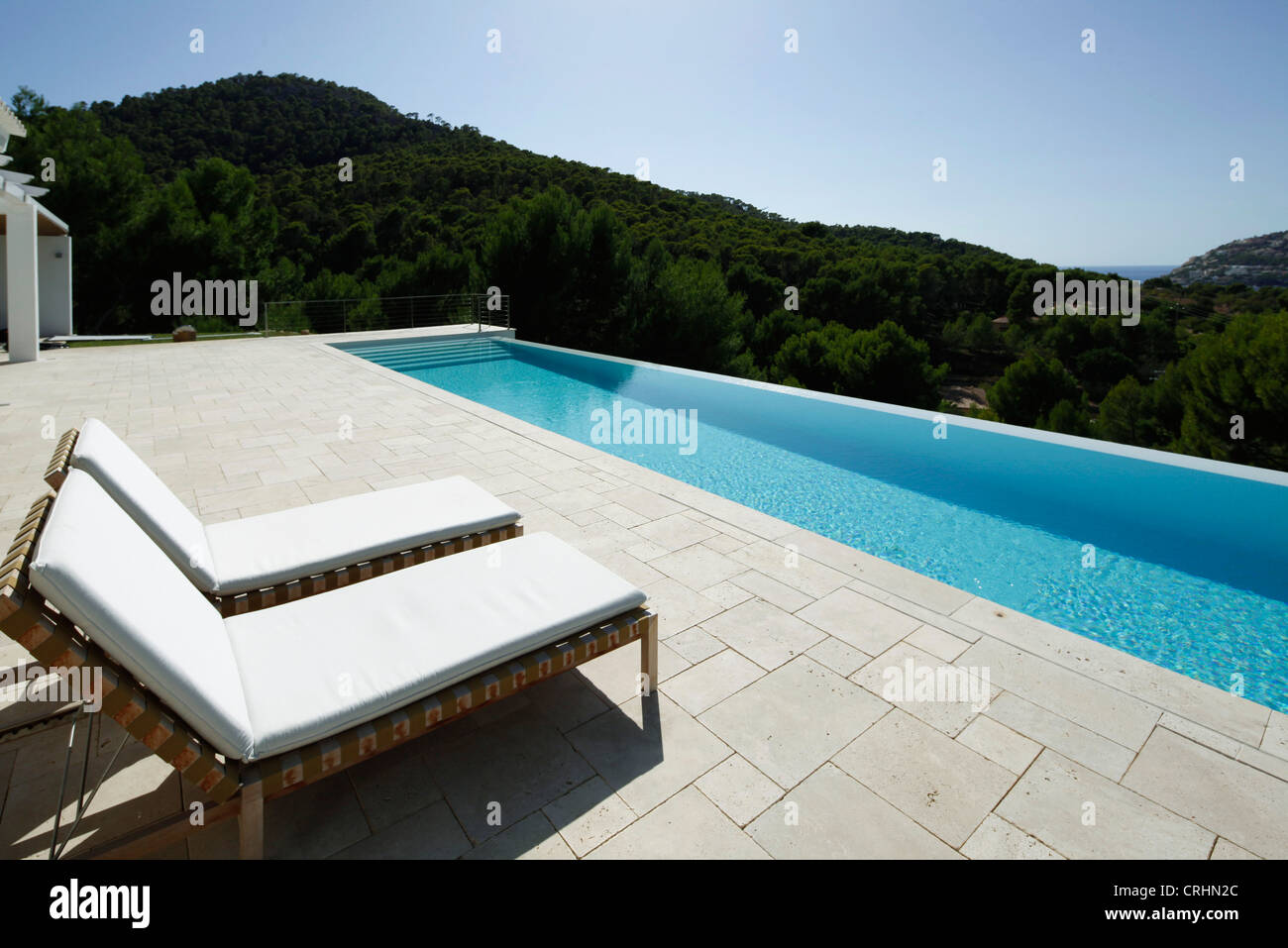 Lounge chairs beside swimming pool Stock Photo