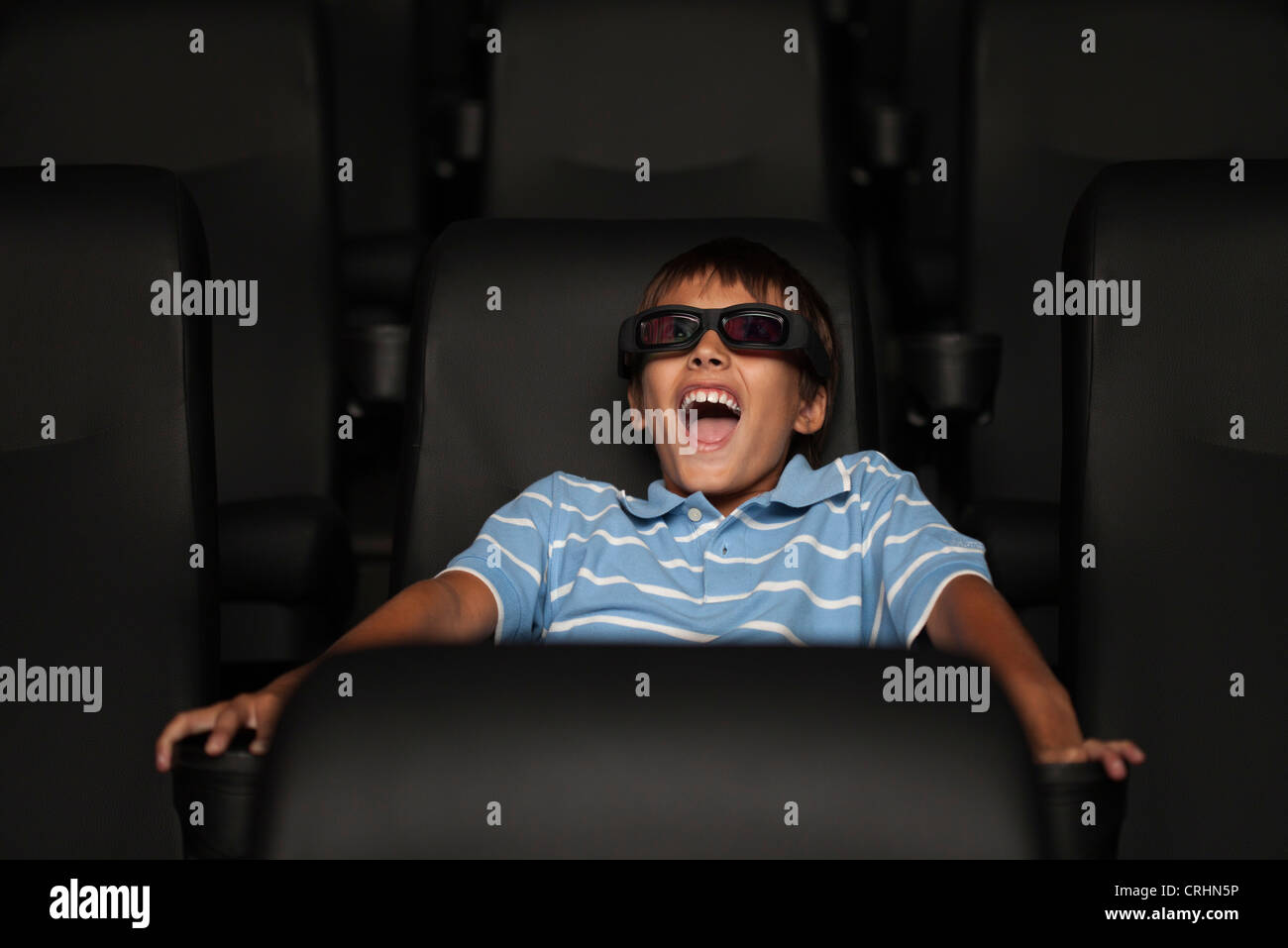 Boy enjoying 3-D movie in theater - Stock Image