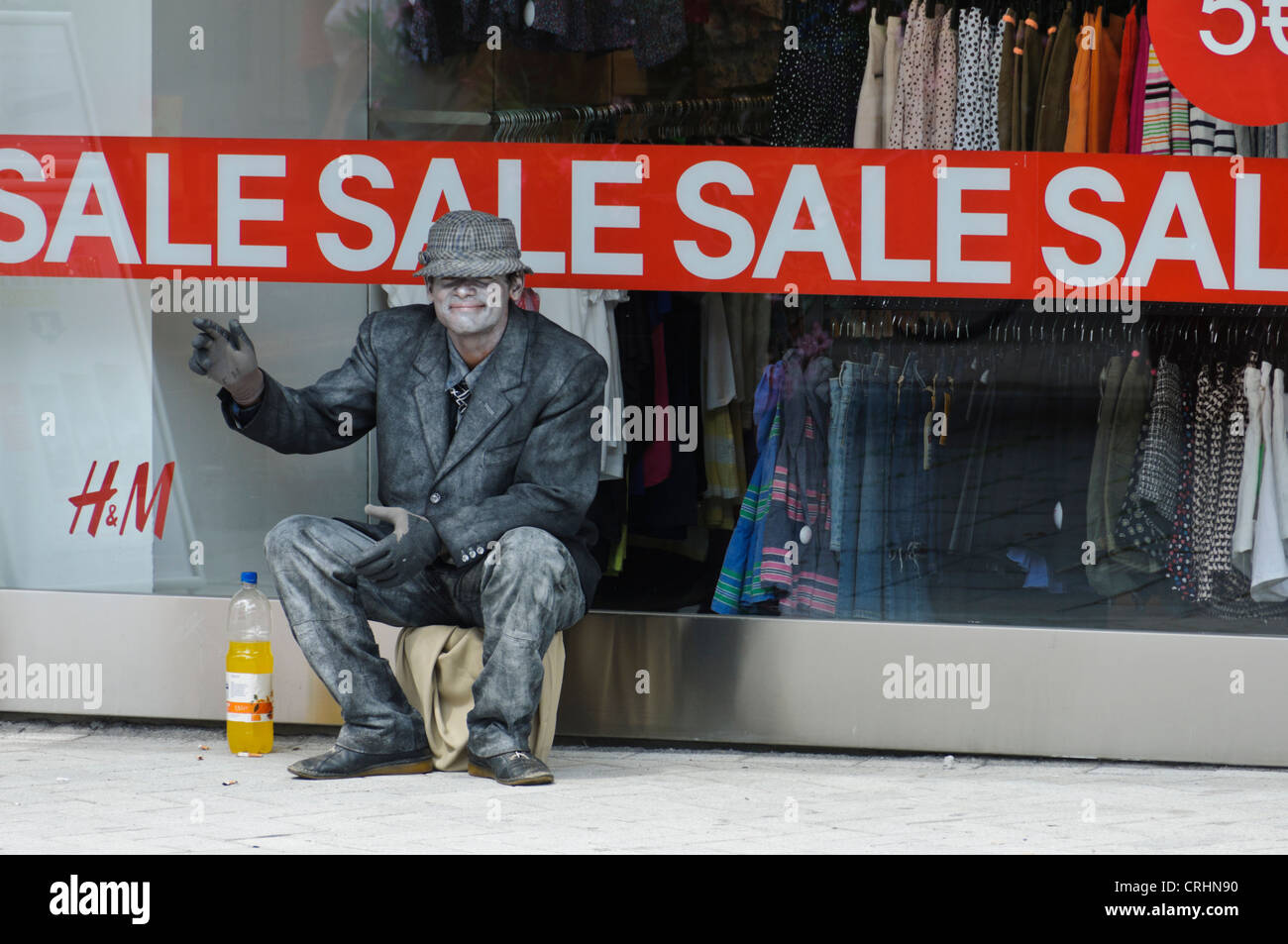 Mime Street Artist sitting in front a H&M Fashion Store Shop Window with 'Sale' Advertisement looking - Stock Image